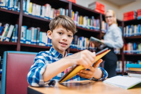 schoolboy holding tablet in library