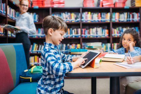 Photo for Cute smiling schoolboy using tablet at library - Royalty Free Image