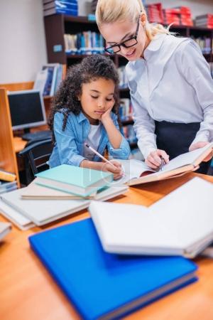 Photo pour Jeune professeur aidant écolière avec des devoirs à la bibliothèque - image libre de droit