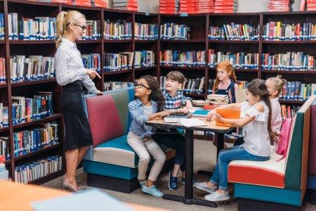 Photo pour Heureux jeune enseignant donner des leçons aux enfants à la bibliothèque - image libre de droit