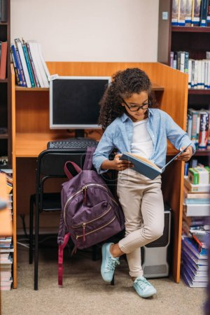schoolgirl reading book in library