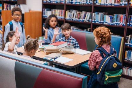 Photo pour Adorables petits enfants levant la main dans la bibliothèque - image libre de droit