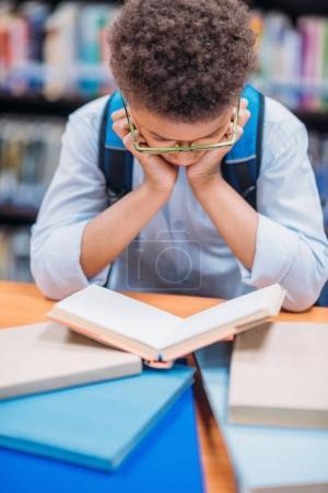 schoolboy reading book in library