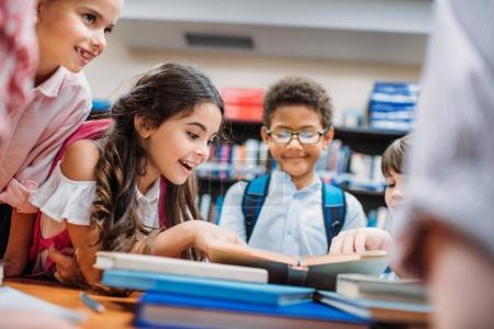 Photo for Excited little children looking at book in library - Royalty Free Image