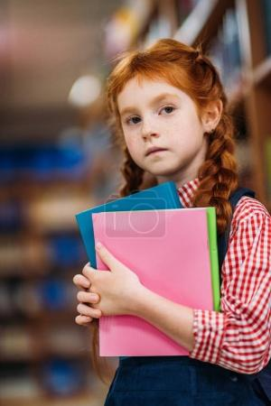 Photo for Serious redhead schoolgirl with books in library - Royalty Free Image