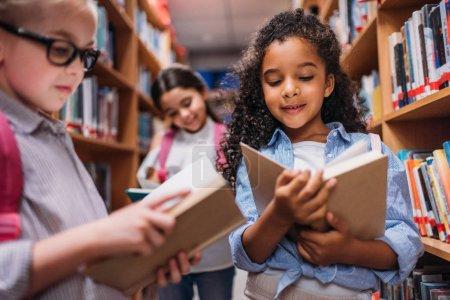 Photo pour Belles petites écolières à la recherche de livres dans la bibliothèque - image libre de droit