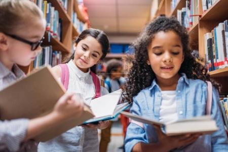 écolières à la recherche de livres dans la bibliothèque