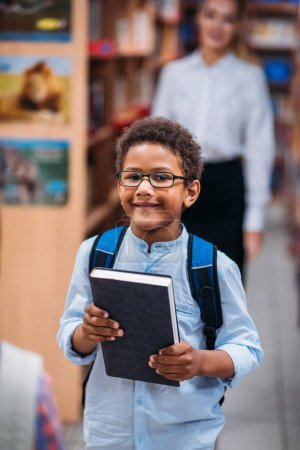 young boy in library with teacher