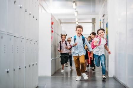 pupils running through school corridor