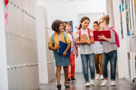 Photo pour Élèves drôles mignons qui traverse le couloir de l'école - image libre de droit