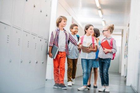 Photo for Adorable happy schoolchildren in school corridor - Royalty Free Image