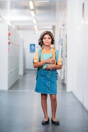 schoolgirl with backpack and book