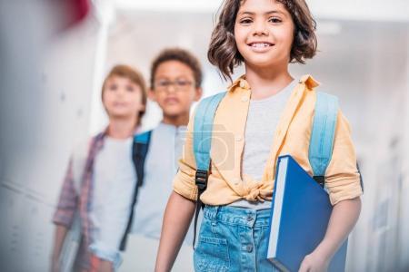 Photo pour Écolière avec sac à dos et livre et garçons à l'école marchant dans le couloir - image libre de droit