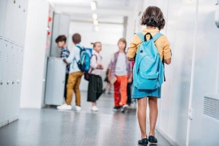Photo pour Petite fille avec sac à dos marchant dans le couloir de l'école - image libre de droit