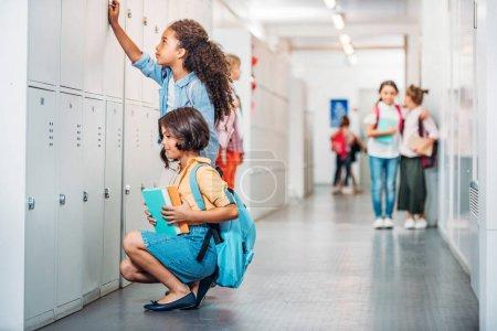 Photo pour Filles ouvrant des casiers dans le couloir scolaire - image libre de droit