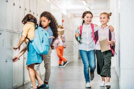 Photo for Adorable little schoolgirls walking through school corridor - Royalty Free Image