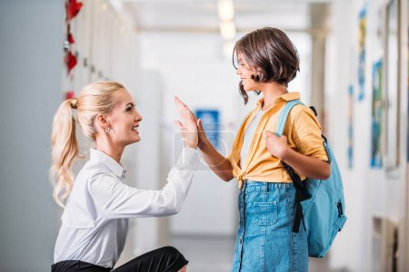 Teacher giving high five to schoolgirl