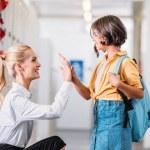 Teacher giving high five to adorable schoolgirl in...
