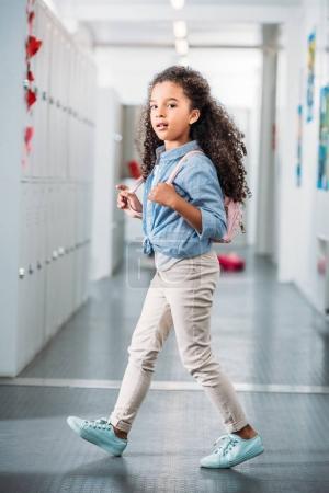 girl walking through school corridor
