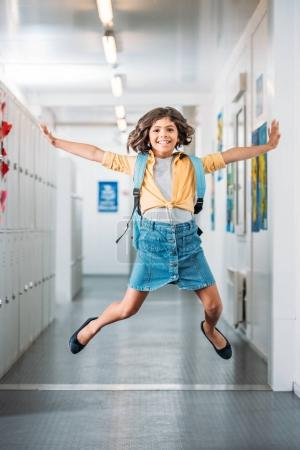 Girl jumping in school corridor
