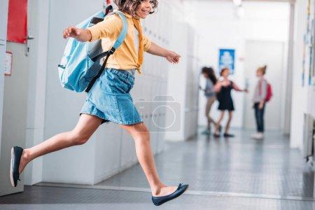 schoolgirl running through school corridor