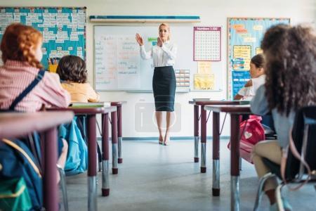 Photo pour Vue arrière des élèves assis sur la leçon en classe et regardant le professeur - image libre de droit
