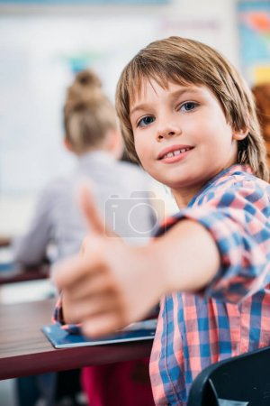 Schoolboy showing thumb up