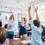 Kids raising hands in class to answer teachers que...