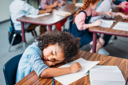 Photo pour Épuisé afro-américaine écolière dormir dans la classe - image libre de droit