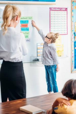 schoolgirl answering next to whiteboard