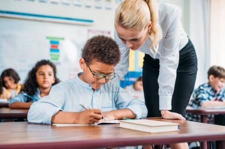 Photo pour Beau jeune enseignant aider heureux écolier avec l'exercice - image libre de droit