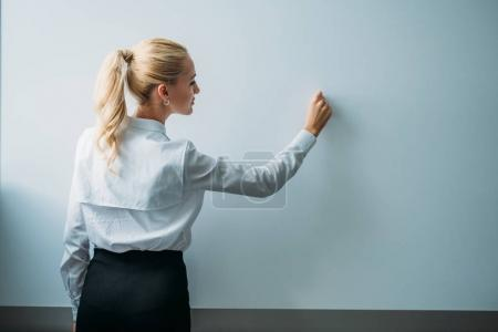 teacher writing on blank whiteboard