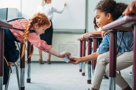 Schoolgirls passing message in class