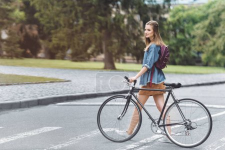 Photo for Happy beautiful girl with bicycle passing the road in park - Royalty Free Image