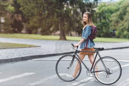 Photo pour MoMA hubava heureuse avec la bicyclette en passant de la route dans le parc - image libre de droit