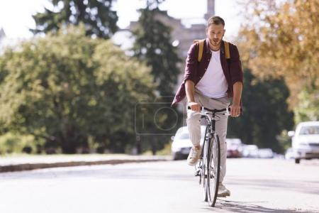 Photo for Concentrated handsome man with backpack riding bicycle in city - Royalty Free Image