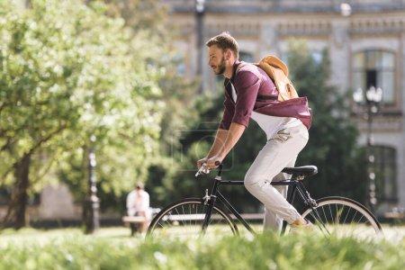 Photo pour Bel homme avec sac à dos, vélo dans le parc - image libre de droit
