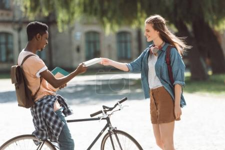 Multiethnic couple with books and bicycle