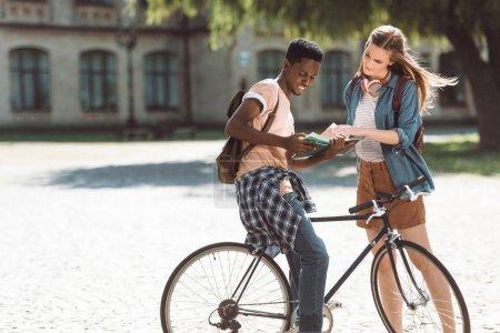 Photo pour Étudiants afro-américains avec vélo et femelle élève lecture convivialité livre près Collège - image libre de droit