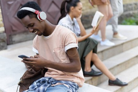 student using smartphone and headphones
