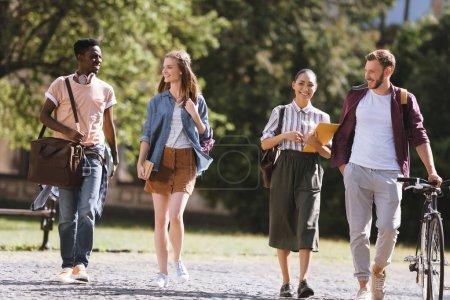 Photo pour Groupe d'étudiants multiculturels heureux marchant ensemble dans le parc - image libre de droit
