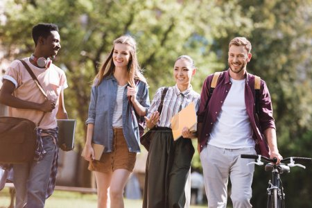 Foto de Grupo de estudiantes multiculturales sonrientes que pasan tiempo juntos en el parque - Imagen libre de derechos
