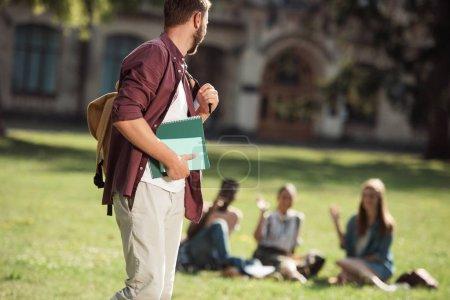 Photo pour Jeune étudiant mâle tenant des livres et regardant des amis assis sur l'herbe près de l'université - image libre de droit