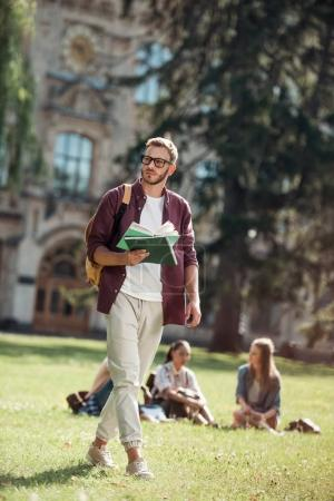 student walking with and reading book
