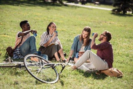 Photo pour Souriant jeunes étudiants multiethniques avec des canettes de soda assis ensemble sur l'herbe verte - image libre de droit