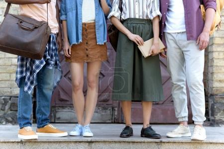 Photo pour Plan recadré de jeunes étudiants multiethniques debout ensemble près du bâtiment de l'université - image libre de droit