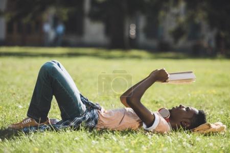 Photo pour Vue latérale du jeune homme afro-américain lisant le livre tout en étant allongé sur l'herbe dans le parc - image libre de droit