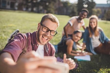 Foto de Enfoque selectivo de amigos multiculturales tomando selfie juntos en el parque - Imagen libre de derechos