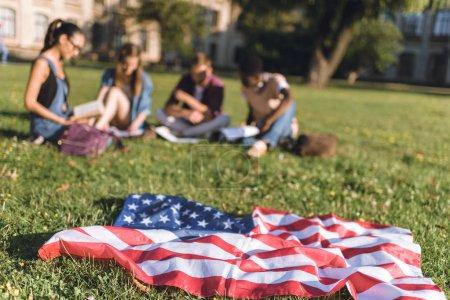 Photo pour Foyer sélectif du drapeau américain et du groupe multiethnique des étudiants sur l'herbe dans le parc - image libre de droit