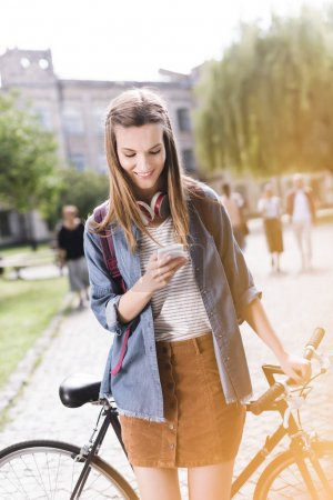 Photo for Young beautiful girl using smatphone and leaning back on bicycle - Royalty Free Image